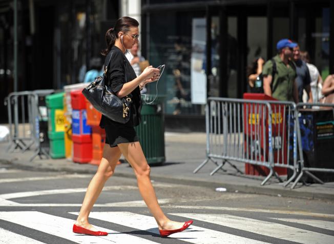 紐約州參議會現正商議一項法案,尋求禁止行人在過馬路時使用手持電子設備,違規者可被罰款25元到250元。(Getty Images)
