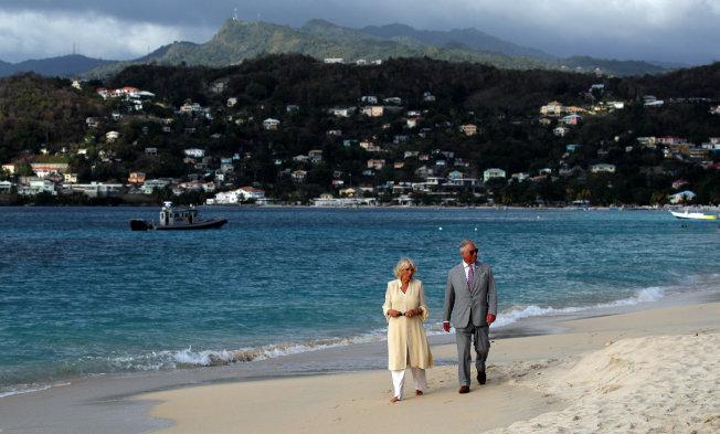 加勒比海島國格瑞那達受到氣候變遷威脅,恐有滅頂之災。圖為英國王儲查理夫婦在格瑞那達海灘散步。(路透)
