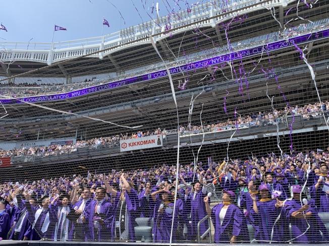 紐約大學第187屆畢業典禮22日在布朗士洋基球場舉行,8000多名學生身著紫袍、頭戴紫帽參加。(記者和釗宇/攝影)