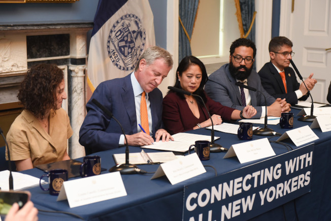 白思豪22日簽署行政令,要求市府所有機關必須每年將一半的紙質與數位廣告費用在少數族裔和社區媒體。(市長辦公室提供)