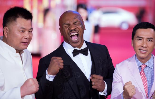 在中國被控詐欺的施建祥(左)在美生活奢華。圖為他2015年6月在上海一項影展上和拳王泰森(中)等合影。(Getty Images)