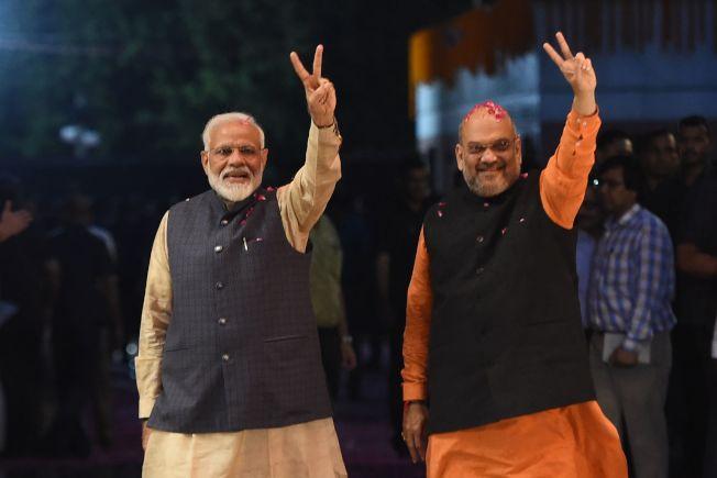 印度總理莫迪(左)與軍師夏哈(右)23日在人民黨總部比出勝利手勢。(Getty Images)