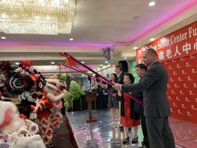 何永康(左一起)、顧雅明及羅一玲等與福壽老人中心籌款晚宴舞獅互動。(記者牟蘭/攝影)