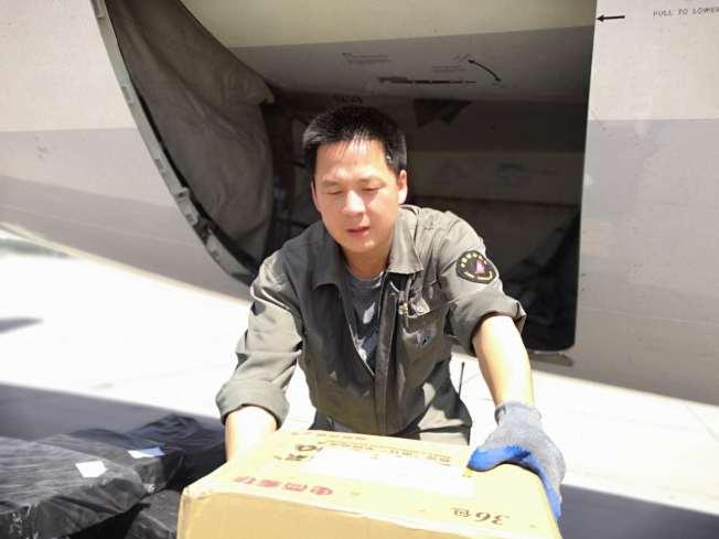 南苑機場行李裝卸小組人員烈日下工作。(取材自新京報)