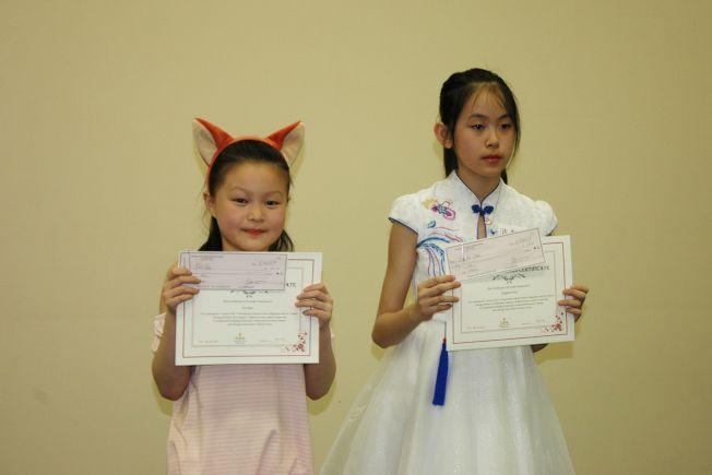 14歲以下兒童組繪畫一等獎得主竇菲(左)和14歲以下兒童組書法一等獎得主游靜雯(右)獲頒發獎狀及獎金。