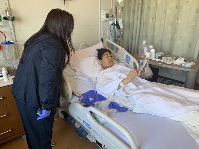 病情惡化被送入醫院搶救的吳國英,由同鄉會的友人照顧她的身體。(記者牟蘭/攝影)