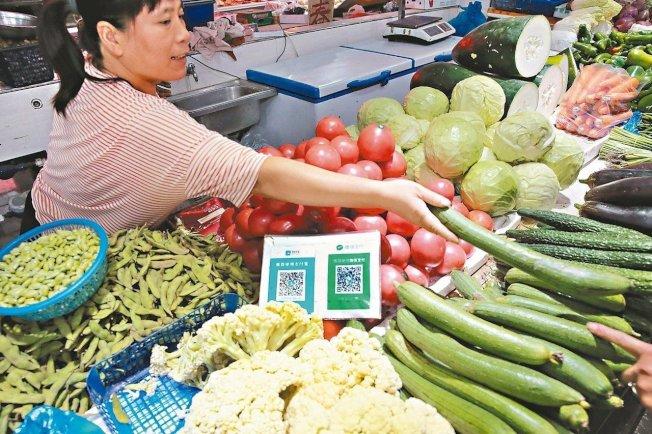 在中國市場買菜,也能使用行動支付。(新華社)