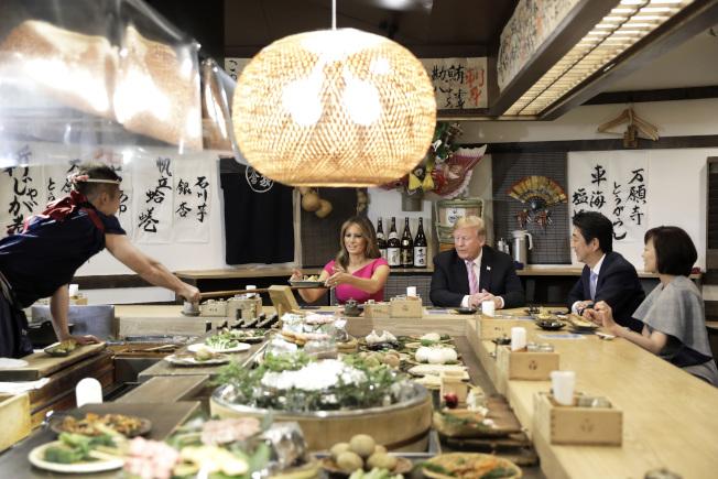 川普總統夫婦與日本安倍首相夫婦26日在東京的六本木的爐端燒店共進晚餐。(美聯社)
