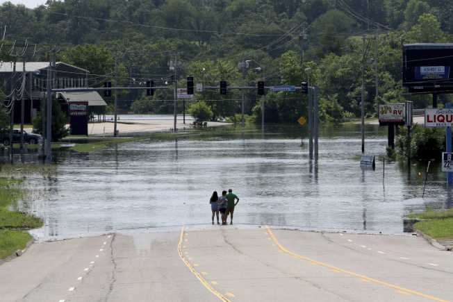 阿肯色州史密斯堡一條道路被洪水淹沒而中斷。(美聯社)