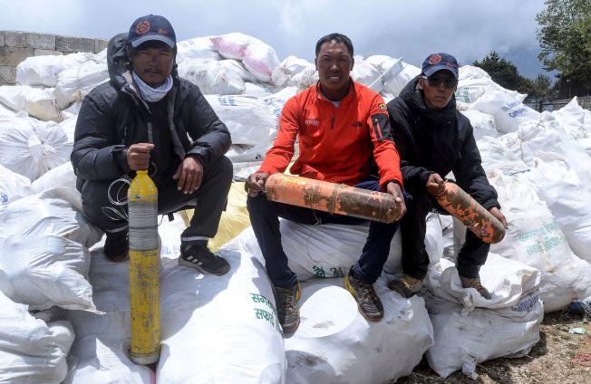 尼泊爾政府登山隊在海拔5270公尺的基地營到海拔7906公尺4號營之間清掃垃圾,挖出高達10公噸的空罐、瓶子、塑膠製品和丟棄的登山裝具,另外還找到4具遺體。圖為清潔隊員坐在垃圾堆上展示「戰果」。(Getty Images)
