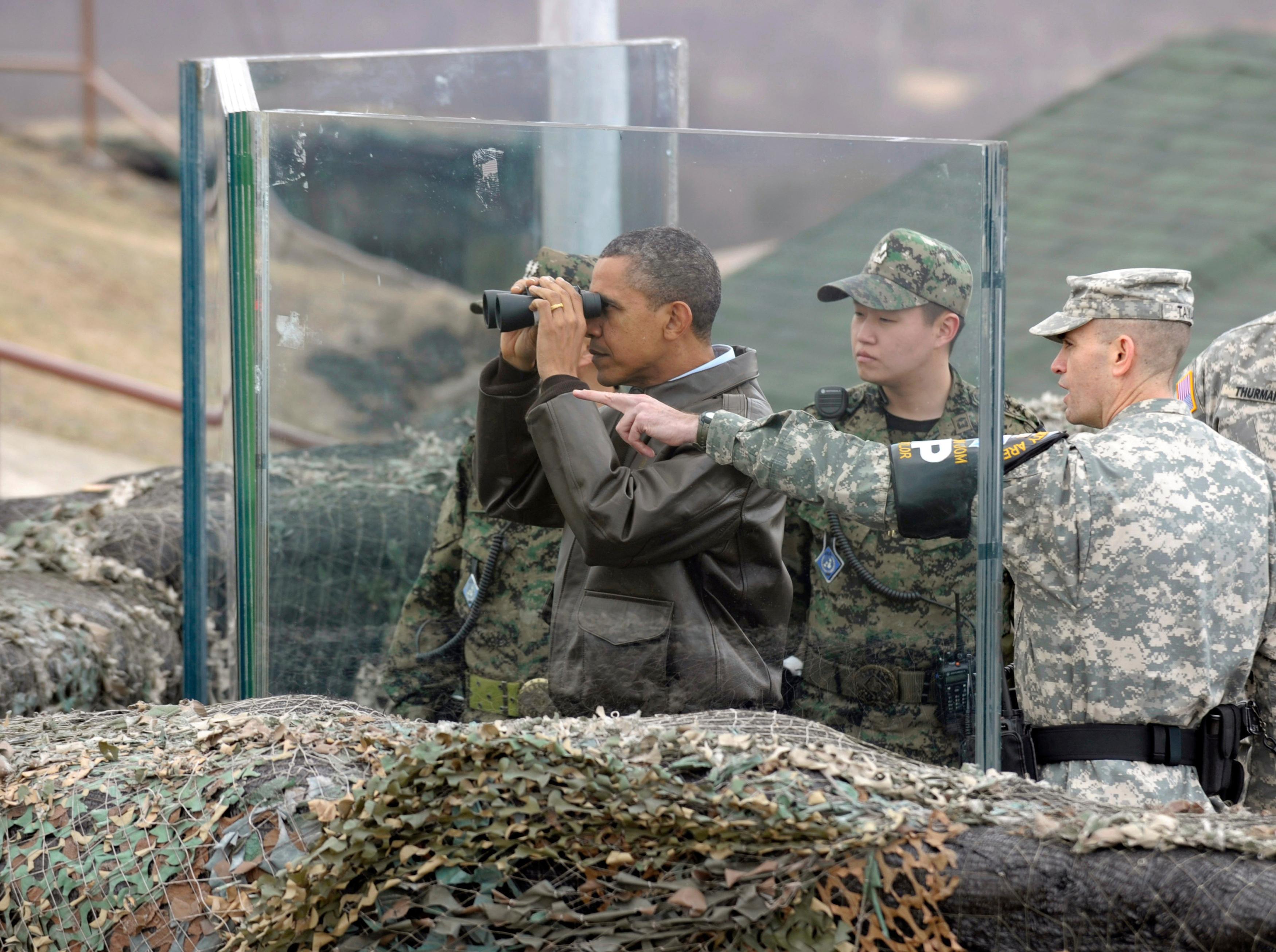 前總統歐巴馬(左)2012年3月25日在DMZ的歐萊特哨所(Observation Post Ouellette)防彈玻璃後方,以望遠鏡觀察北韓境內的一舉一動。(美聯社)