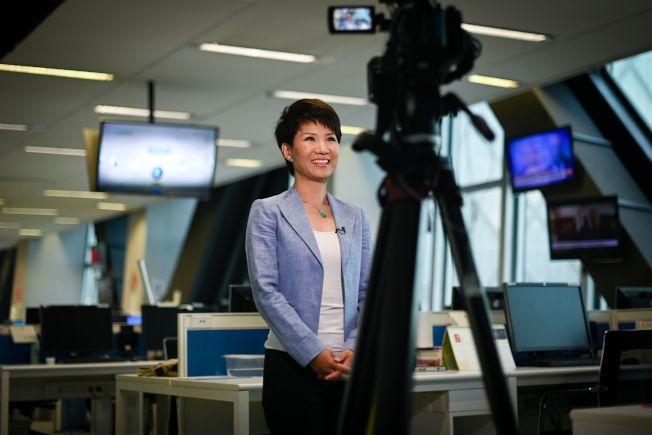 中国国营的环球电视网主持人刘欣与美国福斯商业频道主播翠西. 雷根隔洋对话后,满面笑容接受中国央视采访。 (Getty Images)