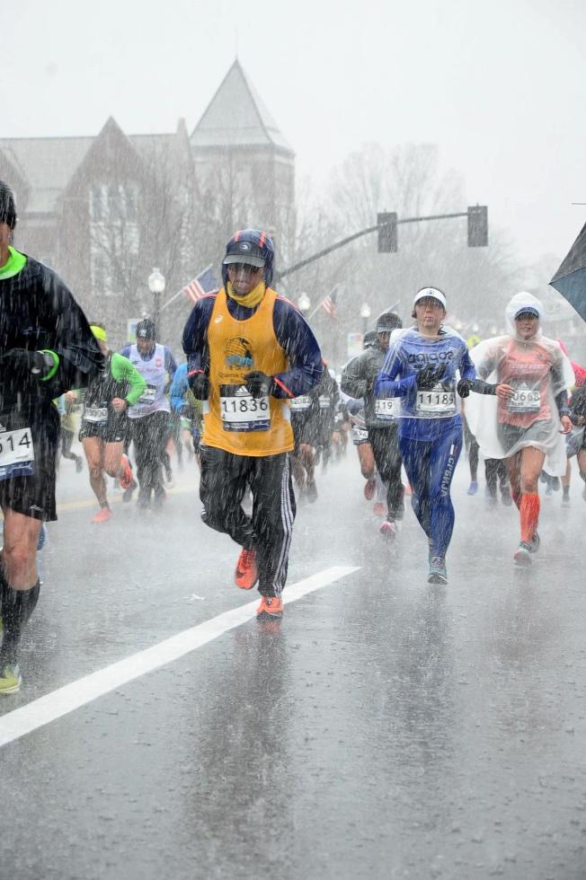 Wiston梅(穿黃色背心)在2018年參加波士頓馬拉松比賽,在雨中跑步。(Wiston梅/提供)