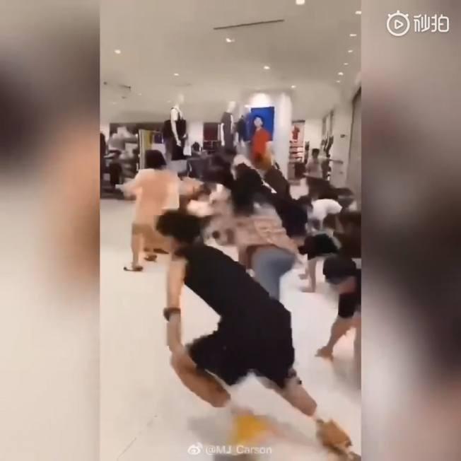 優衣庫店門才剛開三分之一,顧客就迫不及待搶著「爬」進店裡搶購。(取材自微博)