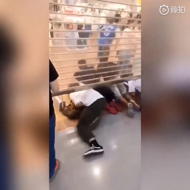 優衣庫店門還沒完全拉開,顧客就「鑽」進店裡搶購。(取材自微博)