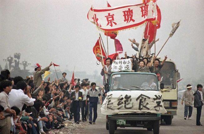 「那個時候,他們還不知道。」1989年5月18日星期四,北京天安門廣場,為了聲援「絕食抗爭中」的中國大學生們,從首都圈各大工廠起身響應的數十萬中國工人,乘著卡車、拉著布條,浩浩湯湯地進了京。 圖/美聯社