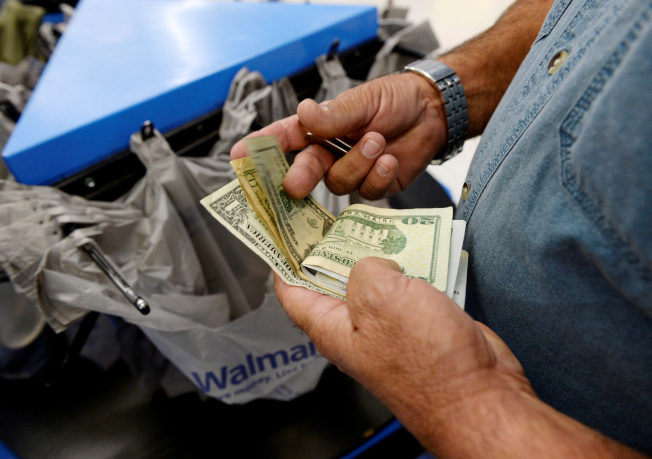 川普總統對墨西哥商品加徵5%關稅,恐將讓全美40萬多個工作機會因此流失。圖為顧客在洛杉磯一家沃爾瑪結帳枱前,清點手上鈔票。(路透)