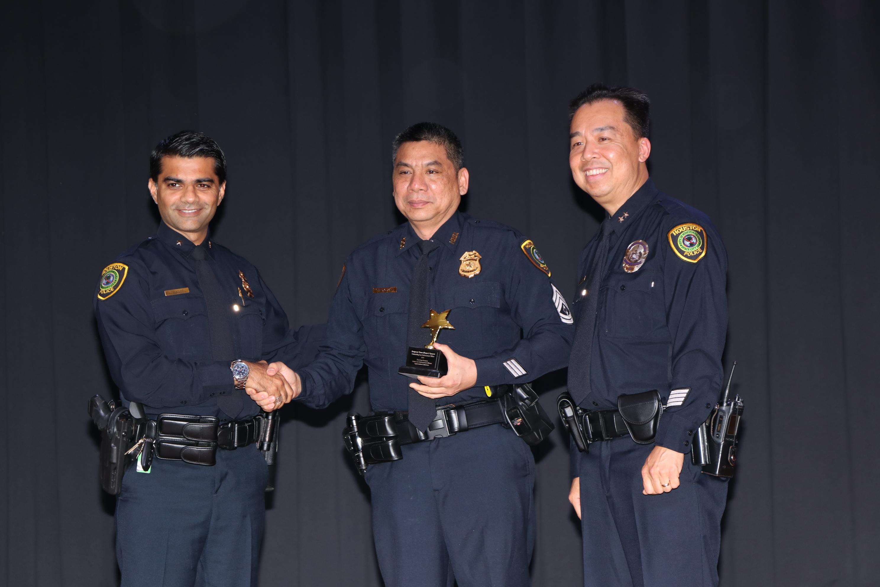 破獲中國城數起打破玻璃案件的警官Roger Nguyen(中)獲副警長Henry Gaw(右)頒獎表揚。