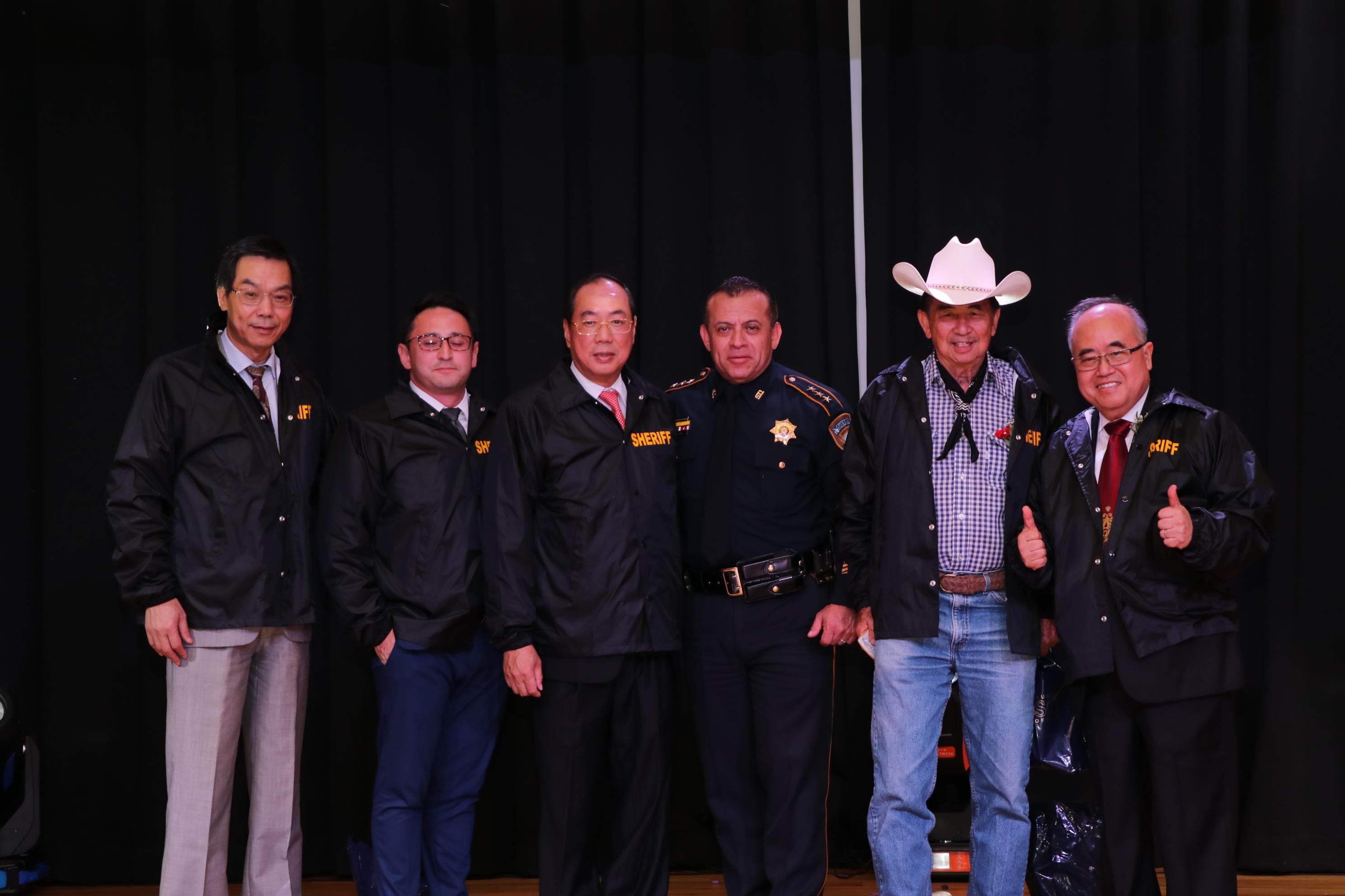 西南管理區區長李雄(右一)等對警方貢獻良多,獲哈瑞斯縣警方頒贈警用外套一件。