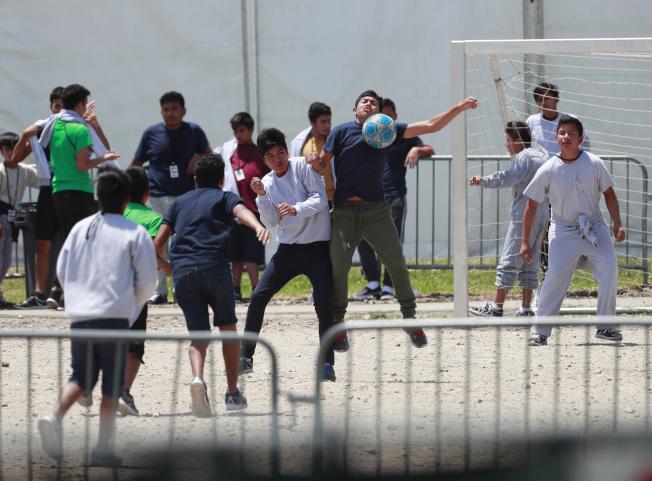 在美墨邊界被逮捕的青少年及兒童,部分被安排住進佛州家園市收容所。圖為被收容的青少年在營中踢足球。(美聯社)