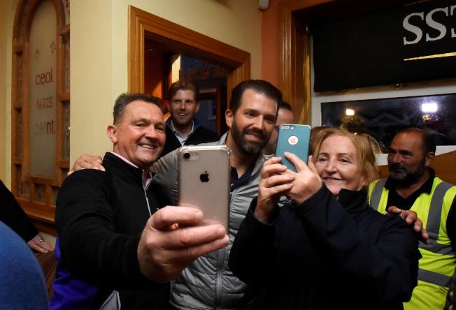 川普的兒子小唐納(中)5日晚到愛爾蘭一家酒吧喝啤酒,和在場人士玩自拍。(路透)