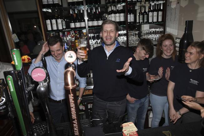 川普的兒子艾瑞克(中)5日晚到愛爾蘭一家酒吧喝啤酒。(美聯社)