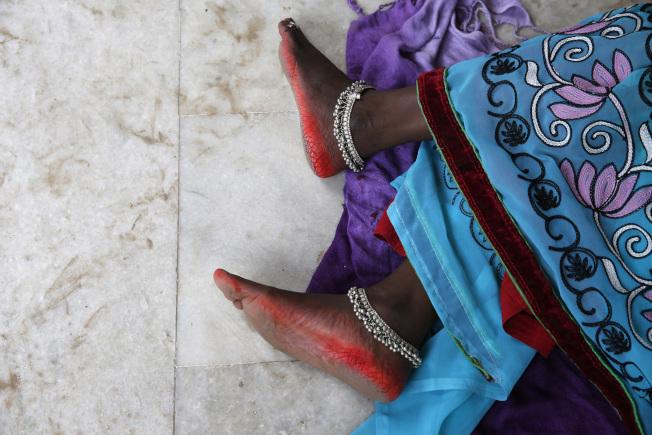 印度連日高溫,圖中這名婦人躺在商店內的大理石地板上驅暑。(美聯社)