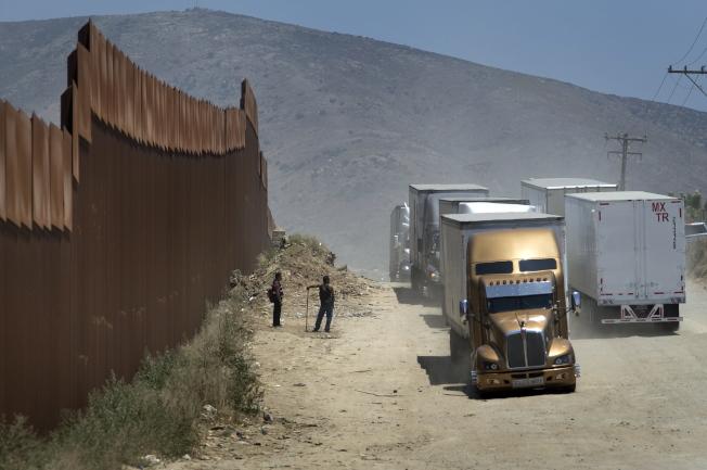 川普總統以對墨西哥的關稅手段,來解決無證移民越界問題。圖為貨櫃車經過美墨邊界圍牆。(歐新社)