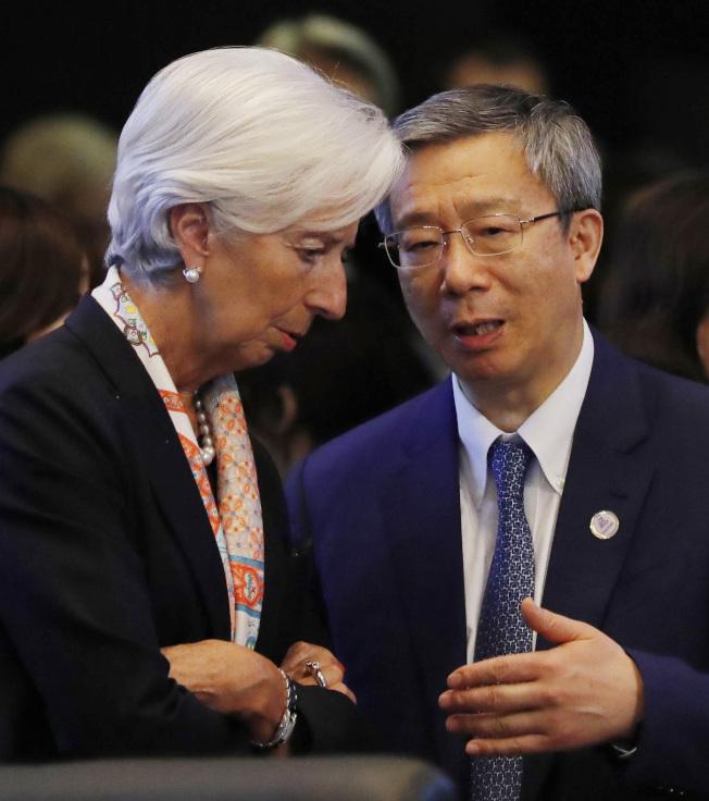 國際貨幣基金總裁拉加德(左)與中國人民銀行行長易綱在G20財長及央行總裁會議上交談。(美聯社)