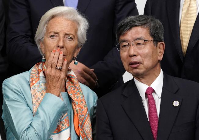 IMF總裁拉加德(左)與亞洲開發銀行總裁中尾武彥(右),9日在G20財長會議大合照時交談。(歐新社)