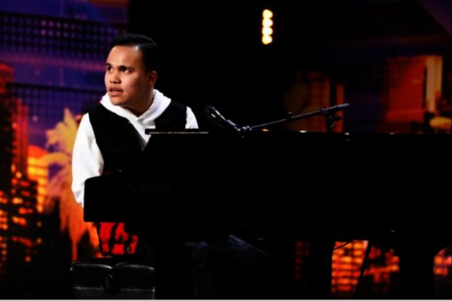 李柯迪坐在鋼琴前,自彈自唱。(NBC美國達人秀)