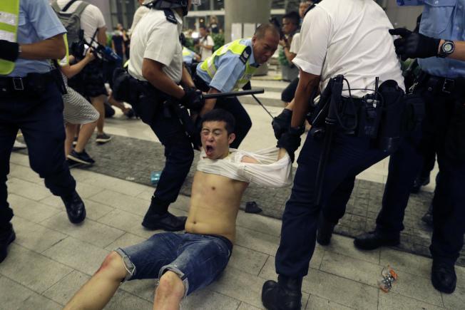 香港「反送中」遊行,警力以警棍、催淚胡椒水清場,並與民眾爆發激烈衝突。(美聯社)