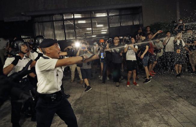 港人反對港府修改「遣返修例」9日出動上街頭大遊行抗議,與維安港警發生多起衝突,港警使用花椒水震退民眾。(美聯社)