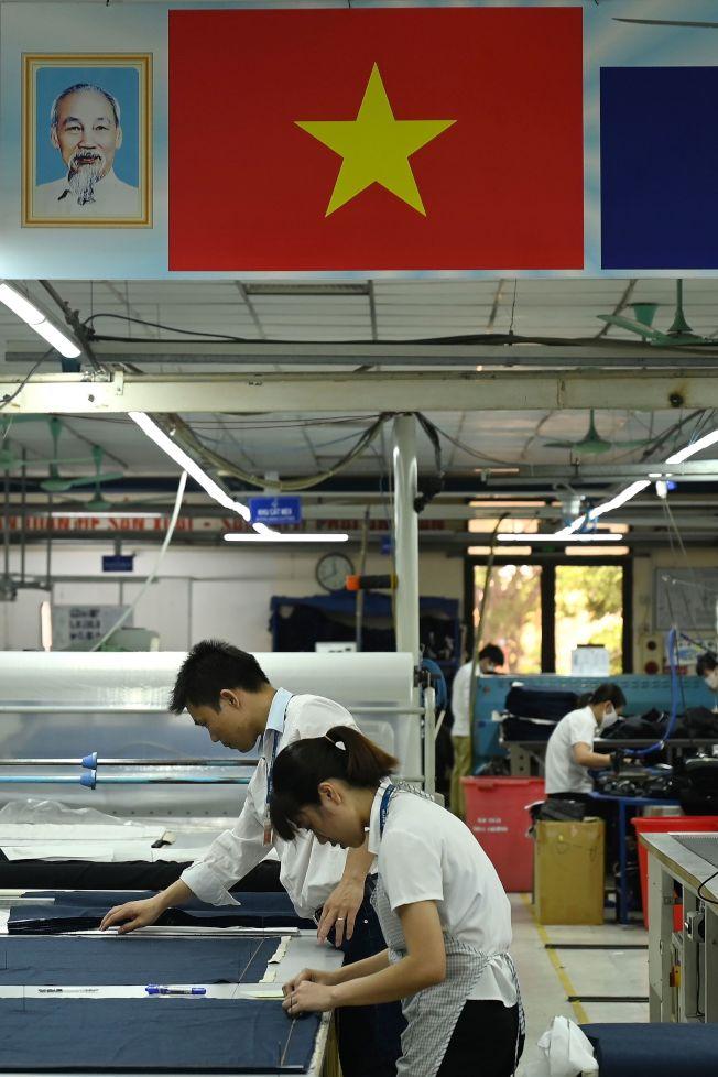 規避美國對中國增加關稅,今年大批中國產品轉到越南出口。資料顯示,自越南出口到美國的貨品量,今年以來暴增。圖為越南河內製衣廠工人在加班趕工。(Getty Images)