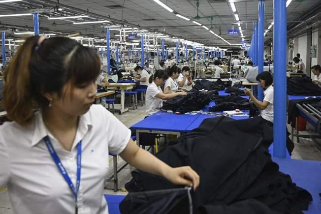 規避美國對中國增加關稅,今年大批中國產品轉到越南出口。資料顯示,自越南出口到美國的貨品量,今年以來暴增。圖為在越南河內製衣廠工人正在加班趕工。(Getty Images)