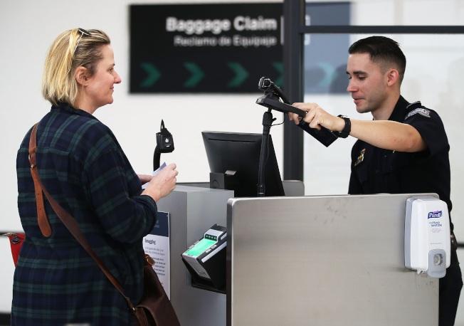 圖為佛州國際機場一名聯邦海關和邊境保護局人員,使用臉部辨識系統對入境旅客查驗身分。(Getty Images)