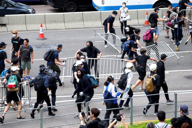香港民眾12日上午在立法會外拆掉拒馬後搬到馬路上試圖占領道路。(特派記者王騰毅/攝影)