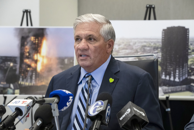 一項訟案控告,2017年發生在倫敦造成72人慘死的格倫費爾大廈毀滅性大火,是多家美國公司使用不良材料所致。圖為律師蒙格魯齊在記者會中發言,後為失火現場照片。(美聯社)