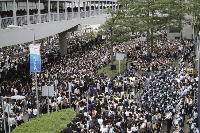 成千上萬示威者包圍特區政府立法會,與鎮暴警察對峙。(美聯社)