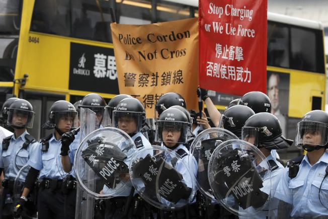 香港警察舉牌要求示威群眾停止衝擊,否則將使用武力。(美聯社)