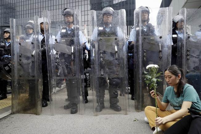 一名女性抗議者手持鮮花,坐在鎮暴警察前面和平抗議。(美聯社)