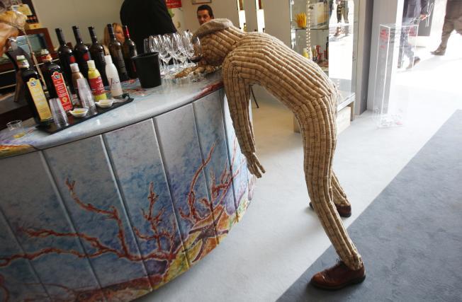 全球最大紅酒盛事「義大利葡萄酒展覽會」(Vinitaly)吧台旁,趴著宿醉人偶。(美聯社)