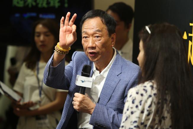 富士康表示,若有必要,可把蘋果公司生產線全部移出中國。圖為鴻海集團董事長郭台銘(中)上月在台北回答鴻海大陸廠區有關提問。(中央社)