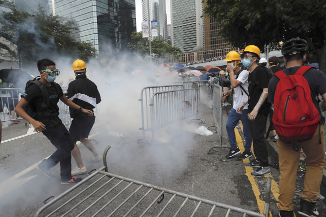 """香港""""反送中""""示威者在立法会外被港警发射催泪瓦斯。香港立法会原订12日进行""""逃犯条例""""修法二读确定推迟,但大批抗议者仍不愿散去,并与下午3时半与警方爆发冲突。美联社"""