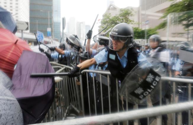 香港警察揮動警棍擊打示威者。(路透)