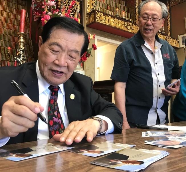 李昌鈺(左)在他的個人名信片上簽名,送給僑領們留念。(記者李秀蘭/攝影)