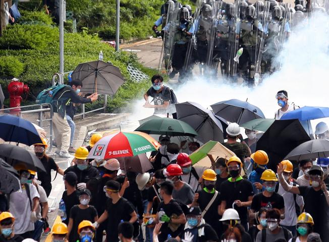 警方正不停發射催淚瓦斯,試圖驅散「違法集結」的示威群眾,群眾以雨傘抵擋向後撤退。(特派記者王騰毅/攝影)