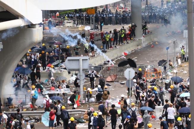 警方正不停發射催淚瓦斯,試圖驅散「違法集結」的示威群眾。立法會全面封鎖,大批員警進入戒備布防,示威者亦向後撤退。(特派記者王騰毅/攝影)