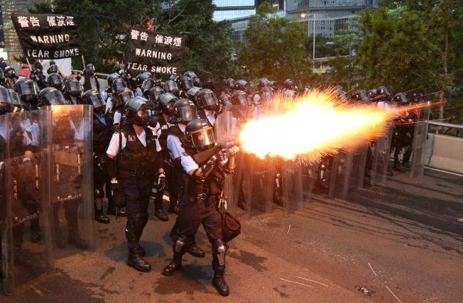 警方向示威群眾發射催淚瓦斯,槍口拖曳一片火光。(路透)
