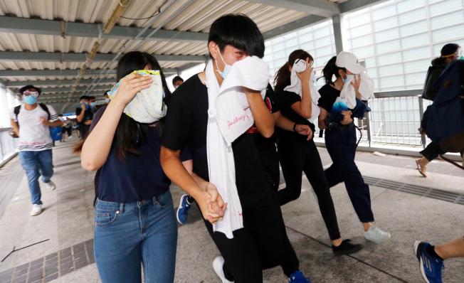 香港警方向示威者發射催淚瓦斯,試圖驅散「違法集結」的人群,部分民眾用毛巾掩住口鼻。(特派記者王騰毅/攝影)